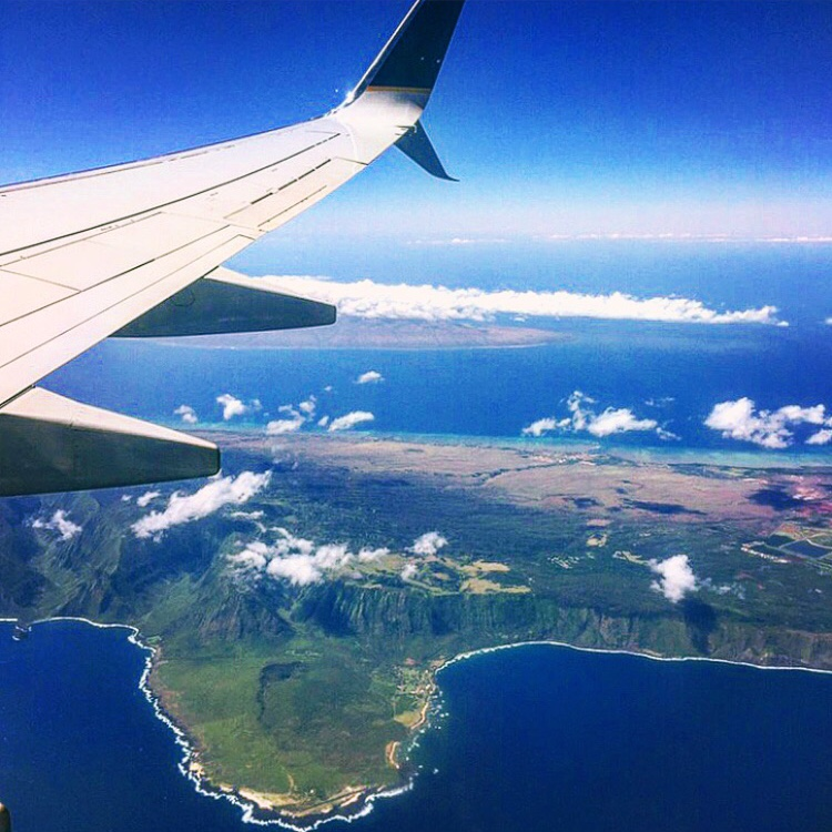 airplane wing over green island Oahu vs. Maui
