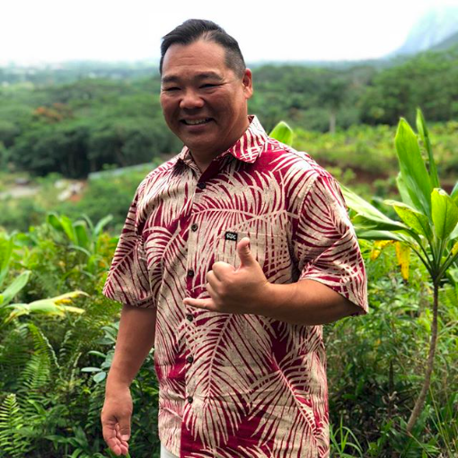 man wearing muted red aloha shirt and waving a shaka