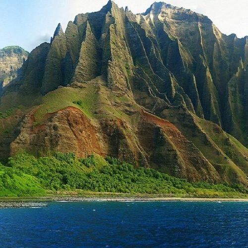 green mountain range on ocean with deep crevices Na Pali coast first time in Hawaii