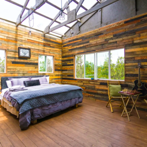 bedroom with glass ceiling and paneled wood treehouses in Hawaii