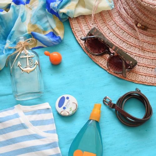 flat lay of beach essentials reef-safe sunscreen