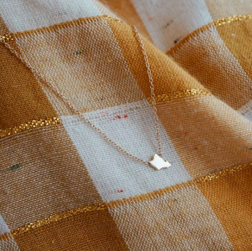 Oahu-shaped necklace on checked orange and white blanket Hawaii artists