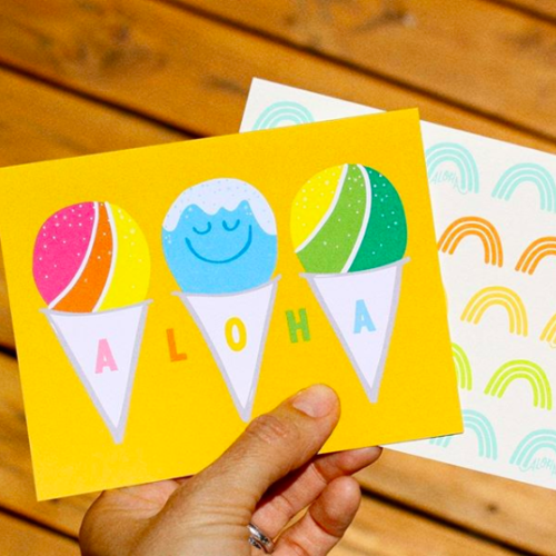 """Hand holding bright yellow card with three shave ice and say """"aloha"""""""