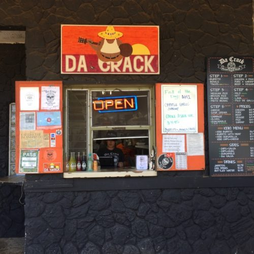 "takeaway counter called ""Da Crack"" covered in black rocks and a bright orange sign"
