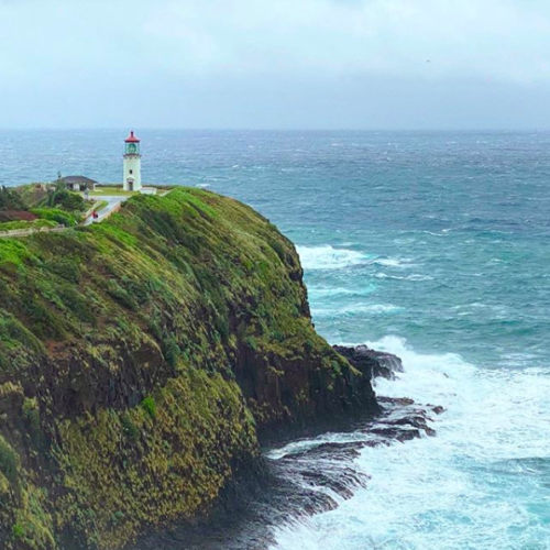 lighthouse on green cliff with crashing waves