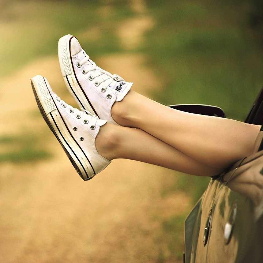 Girl's shoes and legs outside of car window