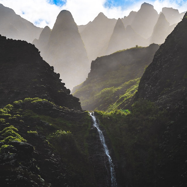 waterfall cascading down with foggy mountain peaks in the background