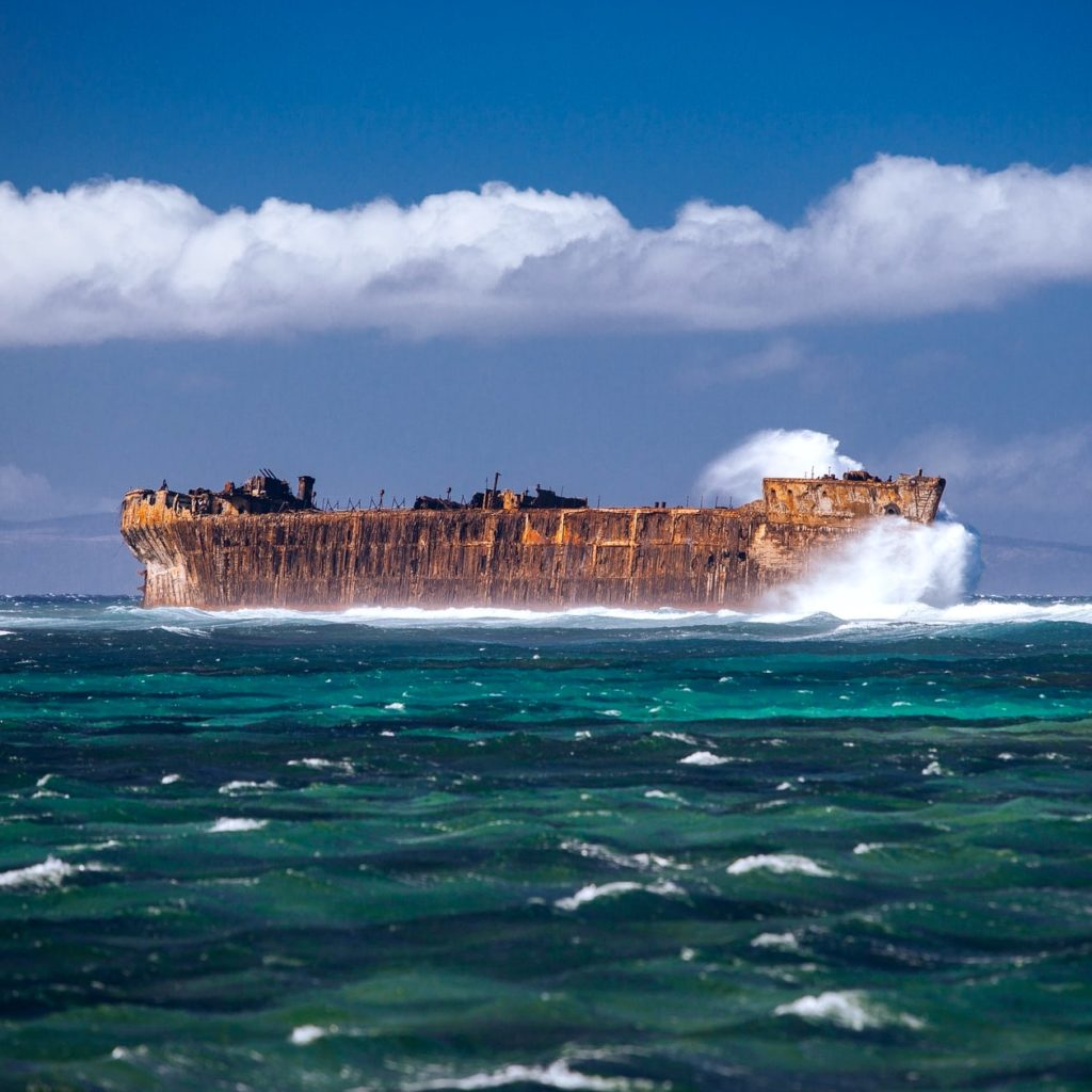 large shipwreck in ocean with wave crashing into it Shipwreck Beach Lanai