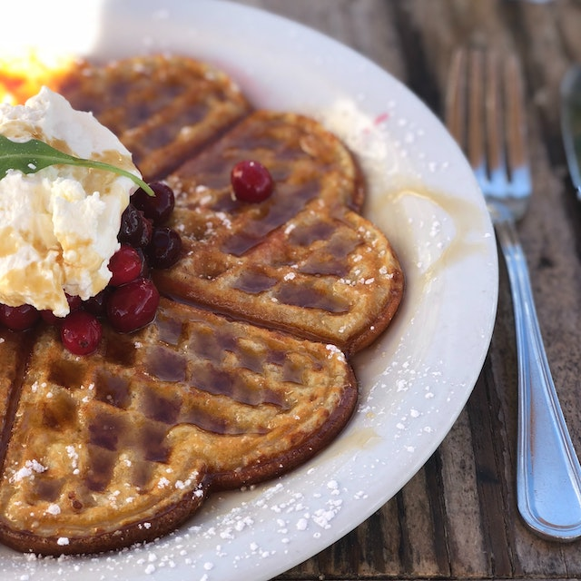 waffle with whipped cream and berries on top